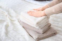 Mulher que dobra toalhas limpas na cama, fotos de stock royalty free