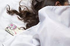 Mulher que dorme com o telefone na cama Mulher Latin imagens de stock