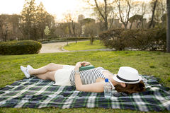 Mulher que dorme com um chapéu sobre sua cara em um parque Fotografia de Stock