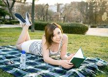 Mulher que dorme com um chapéu sobre sua cara em um parque Foto de Stock Royalty Free