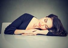 Mulher que dorme em uma mesa fotografia de stock royalty free