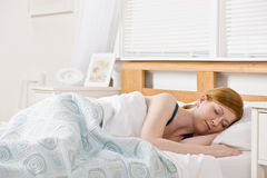 Mulher que dorme na cama imagem de stock
