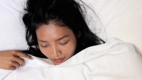 Mulher que dorme na cama video estoque