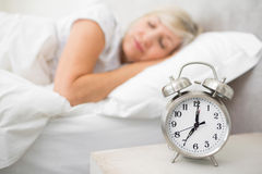 Mulher que dorme na cama com o despertador no primeiro plano no quarto Imagem de Stock