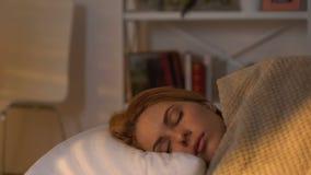 Mulher que dorme na cama confortável, parte externa da luz solar da manhã, sonho saudável filme