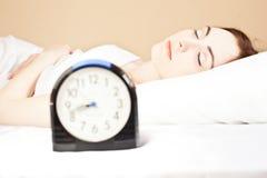 Mulher que dorme na cama (foco na mulher) Fotografia de Stock Royalty Free