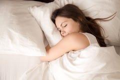 Mulher que dorme na cama que abraça o descanso branco macio