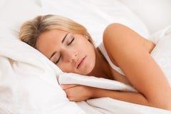 Mulher que dorme na cama. Recreação e sonhos. Imagem de Stock