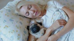 Mulher que dorme no pug do cachorrinho do abraço da cama video estoque