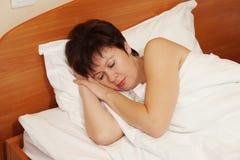 Mulher que dorme sadiamente na cama Fotos de Stock Royalty Free