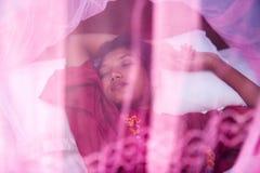 Mulher que dorme sob uma rede de mosquito Fotos de Stock Royalty Free
