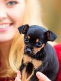 Mulher que embrancing seu cão de cachorrinho Fotografia de Stock Royalty Free