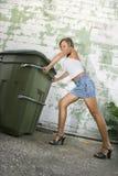 Mulher que empurra o balde do lixo. imagem de stock