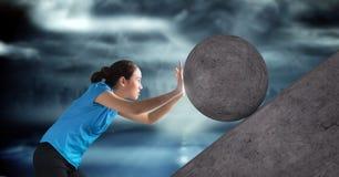 Mulher que empurra o rolamento em volta da rocha imagem de stock