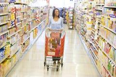 Mulher que empurra o trole ao longo do corredor do supermercado Imagens de Stock