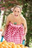 Mulher que empurra o Wheelbarrow enchido com as laranjas Fotografia de Stock