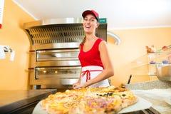 Mulher que empurra a pizza terminada do forno Fotos de Stock