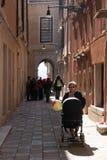 Mulher que empurra um carrinho de criança na cidade velha de Veneza, Itália Foto de Stock Royalty Free