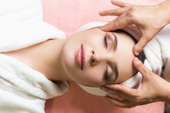 Mulher que encontra-se com olhos fechados e que tem a massagem da cara ou da cabeça nos termas imagem de stock