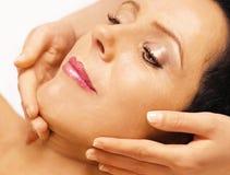 A mulher que encontra-se, começ a massagem, reiki, em sua face Imagem de Stock Royalty Free