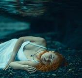 Mulher que encontra-se debaixo d'água foto de stock royalty free