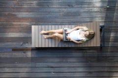 Mulher que encontra-se em de madeira sunbed Imagem de Stock
