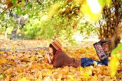 Mulher que encontra-se em seu estômago nas folhas de outono foto de stock