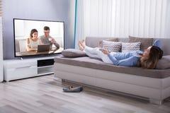 Mulher que encontra-se em Sofa Watching Television foto de stock royalty free