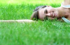 Mulher que encontra-se em um gramado Fotografia de Stock Royalty Free