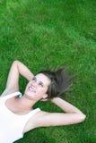 Mulher que encontra-se em um gramado Imagens de Stock Royalty Free