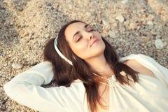 Mulher que encontra-se em uma areia do mar e em uma música de escuta Fotografia de Stock