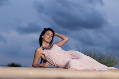 Mulher que encontra-se em uma duna de areia Foto de Stock