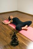 Mulher que encontra-se em uma esteira da ioga - vertical Fotografia de Stock