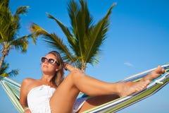 Mulher que encontra-se em uma rede em uma praia Fotos de Stock Royalty Free