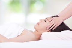 Mulher que encontra-se em uma tabela da massagem em uns termas da saúde Fotos de Stock Royalty Free