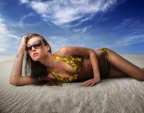 Mulher que encontra-se na areia Fotos de Stock Royalty Free