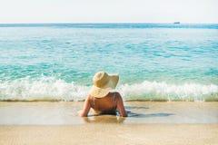 Mulher que encontra-se na areia e que aprecia águas do mar azuis claras Imagem de Stock Royalty Free