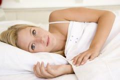 Mulher que encontra-se na cama Imagem de Stock Royalty Free