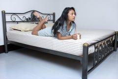 mulher que encontra-se na cama com uma caneca Imagens de Stock Royalty Free