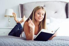 Mulher que encontra-se na cama e que escreve em um diário fotos de stock royalty free