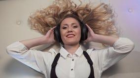 A mulher que encontra-se na cama, escuta a música em fones de ouvido grandes e reage a seu quadro médio sexualmente de sorriso filme