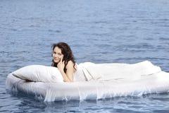 Mulher que encontra-se na cama no mar Imagens de Stock Royalty Free