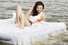 Mulher que encontra-se na cama no mar Foto de Stock Royalty Free