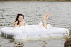 Mulher que encontra-se na cama no mar Fotos de Stock