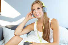 mulher que encontra-se na cama quando música de escuta através do fones de ouvido Foto de Stock Royalty Free