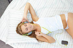 mulher que encontra-se na cama quando música de escuta através do fones de ouvido Fotografia de Stock