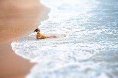 Mulher que encontra-se na costa de mar Fotografia de Stock