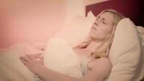 Mulher que encontra-se na dor de sentimento da cama em seu estômago que fricciona a video estoque