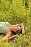 Mulher que encontra-se na grama Foto de Stock