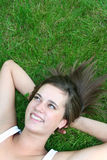 Mulher que encontra-se na grama, sorrindo Fotos de Stock Royalty Free
